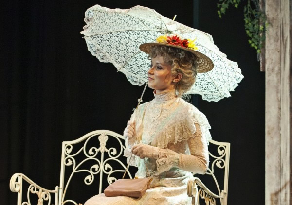 A lady in period clothing sitting on a garden bench holding a parasol